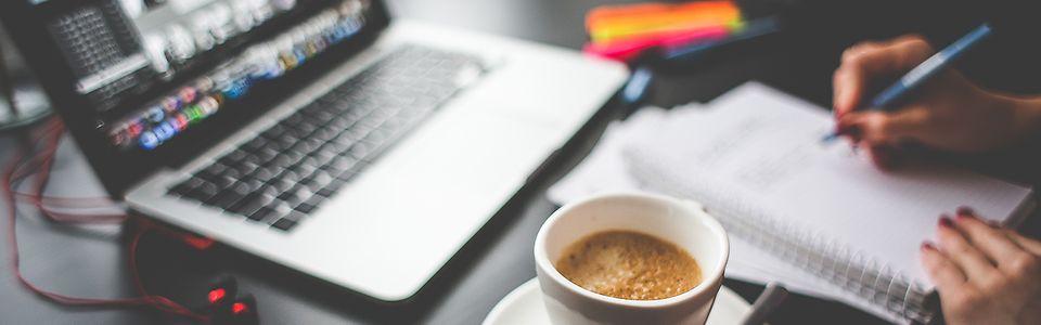 Macbook mit Kaffee, Händen und Schreibblock